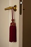 Red tassle. Red Do not disturb tassle hanging on the door in the hotel Royalty Free Stock Photos