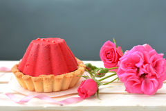 Red, tasty cake with chocolate filling and rose bush on grey background. Close up Stock Images