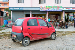 Red Tata Nano. Pokhara, Nepal - NOVEMBER 21, 2013: Red Tata Nano. The Tata Nano is the cheapest car in the world with a price starting at around $2000 in India Royalty Free Stock Images