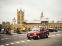 Red taxi cab driving in central London city. United Kingdom Stock Images