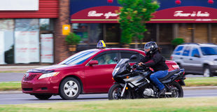 Red taxi and a motorcycle. Red taxi no hands driving and a susuki motorcycle driving side by side in Taschereau street, Brossard, Quebec, Canada Stock Photos