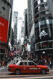 Red taxi waiting on a crosswalk in Hong Kong Island in China stock image
