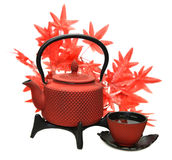 Red tea pot with cup and maple leaves Stock Images