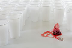 Red teabag beset by a group of white plastic cups, abstract conc Stock Images