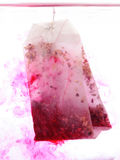 Red Teabag in hot water. In white background Stock Photo
