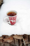 Red teacup with moose in snow. Red mug with spiced tea in the snow Royalty Free Stock Image