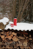 Red teacup and thermos on a snow day. Lifestyle scene with teacup and thermos on a snow covered wood stack Royalty Free Stock Photography