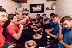 Red team fans are cheering while blue team fans are sad. They are sitting at sports bar. They are watching football game on tv royalty free stock image