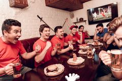Red team fans are cheering while blue team fans are sad. They are sitting at sports bar. They are watching football game on tv royalty free stock photography