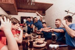 Red team fans are sad while blue team fans are cheering at sports bar. They are watching football game on tv royalty free stock image