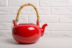 Red teapot closeup on the table. stock photography