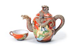 Red teapot with cup. Antique red teapot with dragon and one cup Royalty Free Stock Image