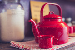 Red teapot and cup on dishcloth Royalty Free Stock Photos