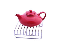 Red teapot on a grill Stock Images
