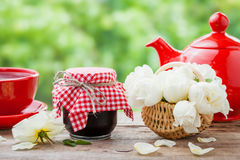 Red teapot, jars of jam, basket with roses bunch Stock Photography