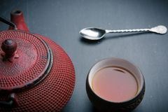 Red teapot and metal spoon and cup of tea royalty free stock image