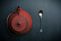 Red teapot and silver spoon on dark background stock photo