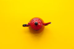 Red teapot on solid yellow background. Very colorful and contrasted Royalty Free Stock Image