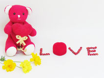 Red teddy bear sit hold the red heart with LOVE lettering made of red seeds and red box of the ring with flowers on white backgrou. Nd. Concept for love on stock photos