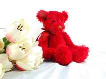Red teddy bear with tulip artificial flowers bouquet Stock Image