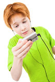 Red teen listens to music. The white background isolated Royalty Free Stock Images