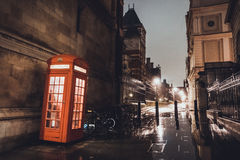 Red telephone booth on a British street. Illuminated red telephone booth on a British city street in a busy commercial district at night on a wet rainy day Stock Image