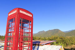 Red telephone booth or public payphone. Old-fashioned traditional red telephone booth or public payphone standing Amidst the mountainous backdrop Stock Photo