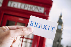Red telephone booth and text Brexit. The hand of a young man showing a signboard with the text Brexit with a red telephone booth and the Big Ben in the Royalty Free Stock Image