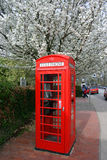 Red telephone box. British red telephone box with blossoming cherry tree in background stock image