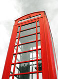 Red telephone box. Iconic british red telephone box abstract with cloudy background Royalty Free Stock Image