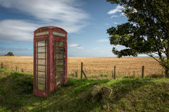Red telephone box in the countryside Stock Images
