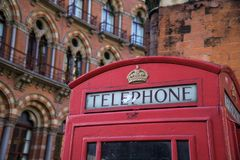 Red Telephone Box in London in front of St Pancras Hotel. royalty free stock images