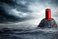 Red telephone box lonely in the ocean Royalty Free Stock Images