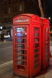 Red Telephone Box in the night in London with light reflections. Stock Photography