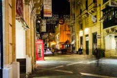 Red telephone box on Republic Street Valletta Malta by night Royalty Free Stock Image
