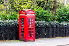 Red telephone box in street with historical architecture in Lond Stock Image