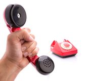 Red telephone handset in hand Royalty Free Stock Image