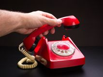 Red telephone handset in hand Stock Photo
