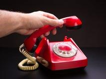 Red telephone handset in hand stock photo