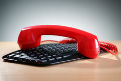 Red telephone receiver on keyboard Royalty Free Stock Photography