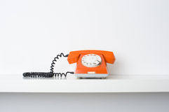 Red telephone on shelf. Picture of retro telephone on shelf. Many lot of copyspace Royalty Free Stock Photography
