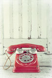 Red telephone on wooden chair Royalty Free Stock Photos
