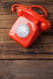 Red telephone on wooden table Royalty Free Stock Photos