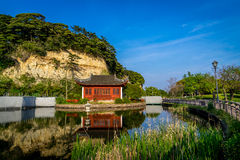 Red temple. Inside the pond with slashed hill behind it, this place is located at local park near many the big factories in honmoku Japan stock image
