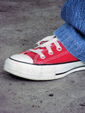 Red Tennis Shoe and Jeans. Closeup of a person wearing red tennis shoes and blue jeans Royalty Free Stock Photo