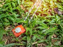Red tent peg holding a rope. Strong red tent peg holding a rope in a green grass ground stock photos