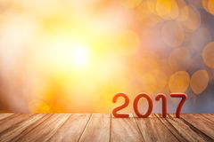 Red 2017 Text on Old Wood Floor on Abstract blur bokeh and flare light. For Happy new year Background Stock Images