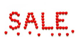 Red Text sale made of round candy dragee. Text sale made of round candy dragee. Creative Composition words sale of red bonbon on white background. Top view. Flat Royalty Free Stock Images