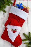 Red textile boot a Christmas with Santa`s head, with gifts and green of spruce branches Royalty Free Stock Image