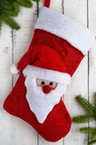 Red textile boot a Christmas with Santa`s head, green branches of spruce Stock Images